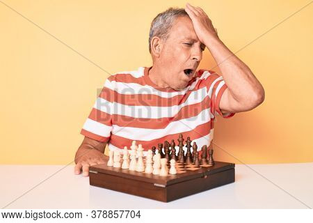 Senior handsome man with gray hair playing chess sitting on the table surprised with hand on head for mistake, remember error. forgot, bad memory concept.