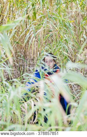 Girl Hiding Behind A Bush In The Woods