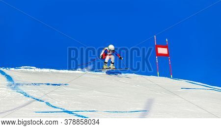 Woman Mountain Skier On Track Of Giant Slalom In Background Blue Sky