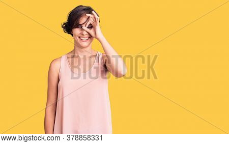 Beautiful young woman with short hair wearing casual style with sleeveless shirt doing ok gesture with hand smiling, eye looking through fingers with happy face.