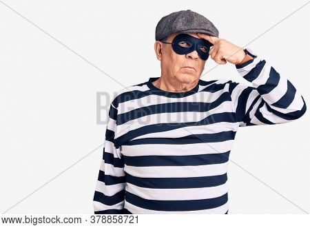 Senior handsome man wearing burglar mask and t-shirt pointing unhappy to pimple on forehead, ugly infection of blackhead. acne and skin problem