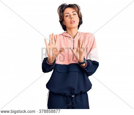 Young beautiful woman wearing sportswear moving away hands palms showing refusal and denial with afraid and disgusting expression. stop and forbidden.