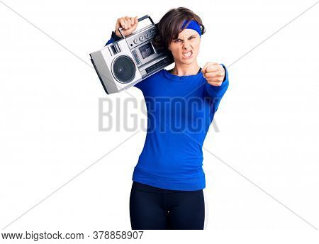 Beautiful young woman with short hair wearing workout clothes and holding boombox annoyed and frustrated shouting with anger, yelling crazy with anger and hand raised