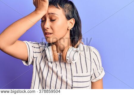 Young woman listening to music using headphones surprised with hand on head for mistake, remember error. forgot, bad memory concept.