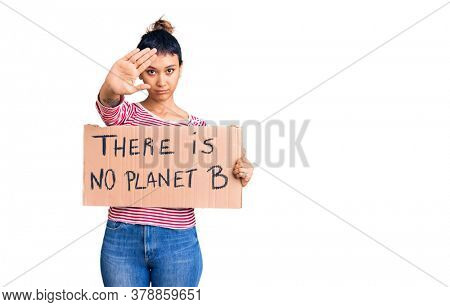 Young woman holding there is no planet b banner with open hand doing stop sign with serious and confident expression, defense gesture