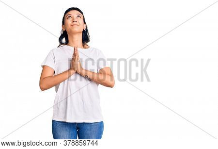 Young woman wearing casual clothes begging and praying with hands together with hope expression on face very emotional and worried. begging.