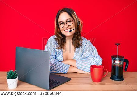 Young beautiful caucasian woman working at the office wearing operator headset happy face smiling with crossed arms looking at the camera. positive person.