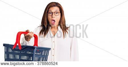Middle age latin woman holding supermarket shopping basket scared and amazed with open mouth for surprise, disbelief face