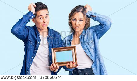 Couple of women holding empty frame confuse and wondering about question. uncertain with doubt, thinking with hand on head. pensive concept.