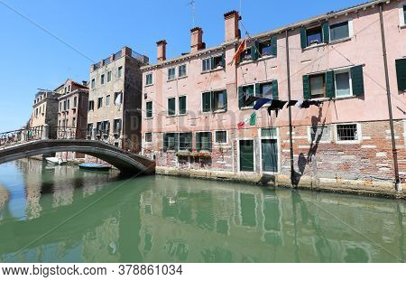 Waterway In Venice With The Clothes Hanging And The Italian Flag Without People
