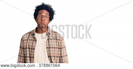 Handsome african american man with afro hair wearing casual clothes and glasses puffing cheeks with funny face. mouth inflated with air, crazy expression.