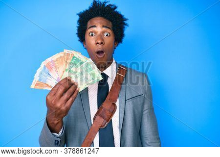 Handsome african american man with afro hair holding south african rand banknotes scared and amazed with open mouth for surprise, disbelief face
