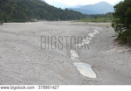 Tagliamento River And The Water That Disappears Among The Stones Due To The Karst Phenomenon In Nort