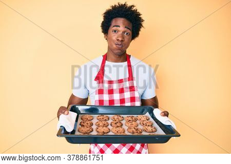 Handsome african american man with afro hair wearing baker uniform holding homemade cookies puffing cheeks with funny face. mouth inflated with air, catching air.