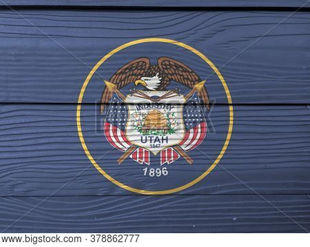 Utah Flag Color Painted On Fiber Cement Sheet Wall Background. The Seal Of Utah Encircled In A Golde