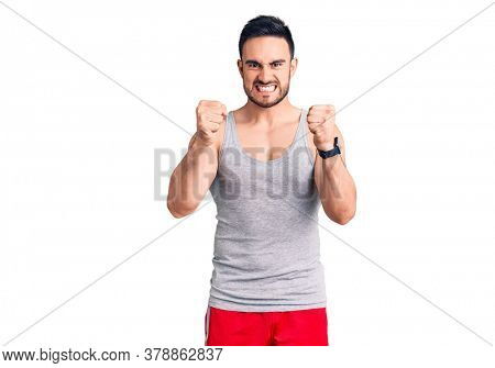 Young handsome man wearing swimwear and sleeveless t-shirt angry and mad raising fists frustrated and furious while shouting with anger. rage and aggressive concept.