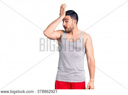 Young handsome man wearing swimwear and sleeveless t-shirt surprised with hand on head for mistake, remember error. forgot, bad memory concept.