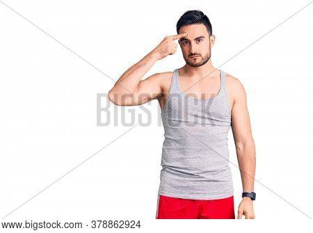 Young handsome man wearing swimwear and sleeveless t-shirt pointing unhappy to pimple on forehead, ugly infection of blackhead. acne and skin problem
