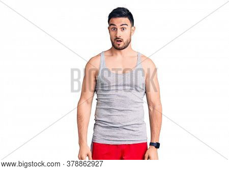 Young handsome man wearing swimwear and sleeveless t-shirt in shock face, looking skeptical and sarcastic, surprised with open mouth