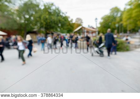 Blurred Crowd Of People Looking Busy In Suburban City Street Near The Well In Sweden