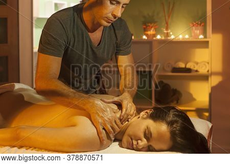 Men's Hands Make A Therapeutic Shoulder Massage For A Girl Lying On A Massage Couch In A Massage Spa