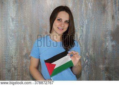 A Young Smiling Woman With A Palestine Flag In Her Hand. Immigration And The Study Of Foreign Langua