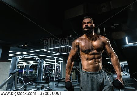 Portrait Of Strong Handsome Fit Man Exercising In Gym With Dumbbells