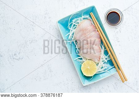Sashimi From Slices Of Raw White Fish Fillet On A Blue Plate On A White Background.