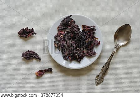 Portion Of Dry Hibiscus Or Sudanese Rose Petals On A White Saucer. Dried Hibiscus Petals. Alternativ