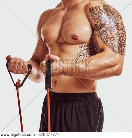 Closeup Of Strong Muscular Athletic Bodybuilder With Tattoo On Biceps Training With Expander