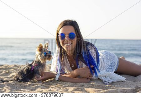 Cheerful Pretty Young Woman In Blue Retro Sunglasses And Blue Hair Sitting Next To Her Dog Yorkshire