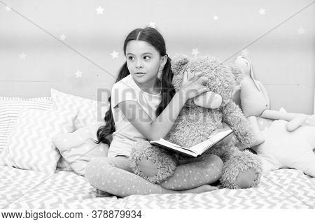 Home Reading. Cute Literature Reader In Bedroom. Little Child Read Book To Teddy Bear Toy. Childrens