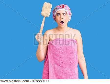 Young caucasian woman wearing shower cap and towel holding sponge scared and amazed with open mouth for surprise, disbelief face