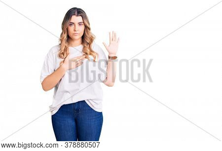 Young caucasian woman wearing casual clothes swearing with hand on chest and open palm, making a loyalty promise oath