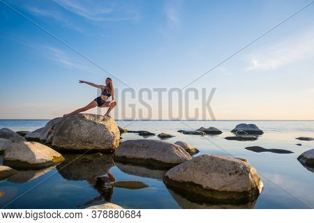 Full body young woman in underwear doing Skandasana pose on rock against sunset sky while doing yoga near peaceful sea in evening
