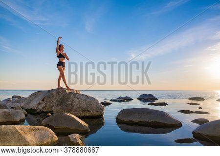 Full length slim female in underwear doing yoga on rock against cloudy sundown sky near calm sea