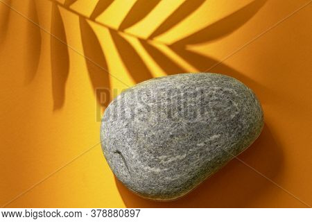 Tropical plant leaf and pebble stone on yellow paper background. Top view, minimal design template with copyspace.