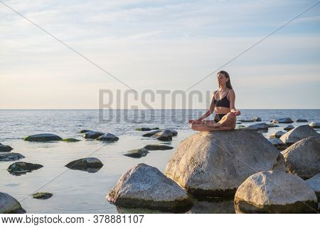 Young female sitting on boulder in Lotus pose and meditating against cloudy sky while doing yoga on seashore