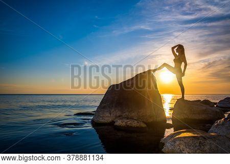 Full length fit woman in underwear doing splits on rocks against cloudy sundown sky in evening on seashore