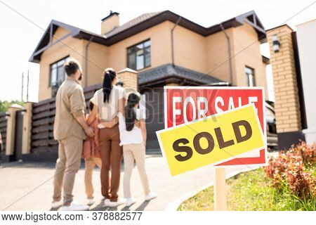 Family with kids cuddling each other and looking at new house, focus on Sold sign