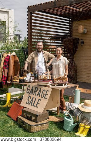Portrait of positive young couple standing at table with useless things and selling it at garage sale in backyard