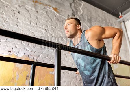 fitness, sport, bodybuilding and people concept - young man doing triceps dip exercise on parallel bars in gym
