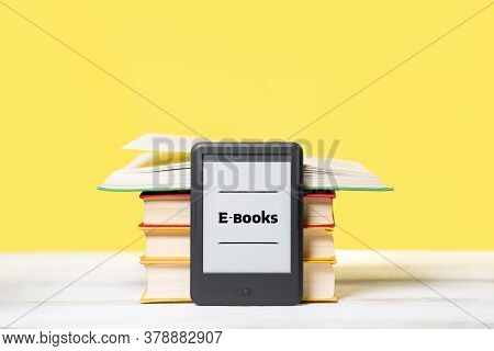 Knowledge. E-book Reader And A Stack Of Books On A Yellow Background. Copy Space. Concept Of Educati