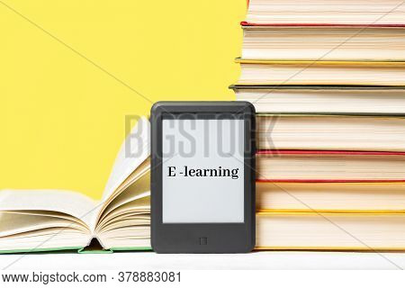 E-learning. E-book Reader And A Stack Of Books On A Yellow Background. Concept Of Education And Elec