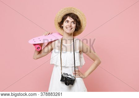 Smiling Tourist Girl In Summer Dress Hat With Photo Camera Isolated On Pink Background. Traveling Ab