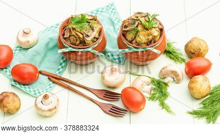 Baked Potatoes With Mushrooms And Meat At Home In The Oven In A Clay Pot. On A Light Green Backgroun
