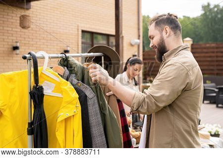 Smiling bearded man in shirt standing at rack and choosing clothes at yard sale