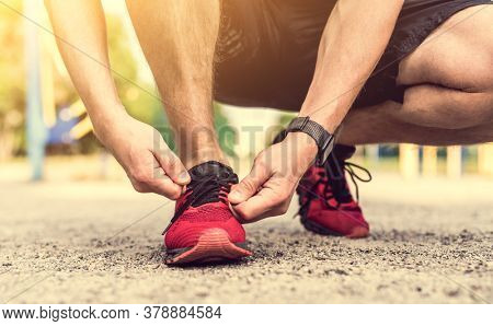 Man tying shoelace on red sneakers during street workout, close up view