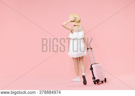 Back Rear View Of Young Tourist Girl In Summer Dress Hat With Suitcase Isolated On Pink Background.