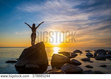 Back view of anonymous female with outstretched arms standing on boulder near calm sea and enjoying freedom against cloudy sundown sky